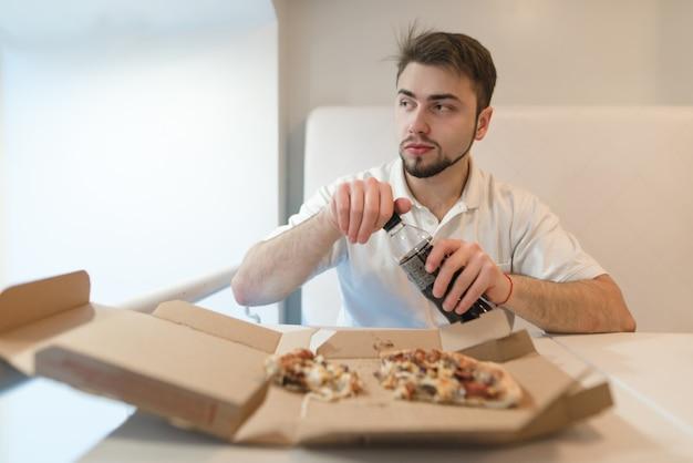 Een man opent een fles met een drankje op de achtergrond van pizza. een man drinkt een pizza met een cola.