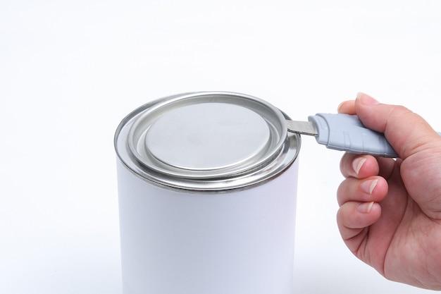 Een man opent een pot witte verf met een blikopener