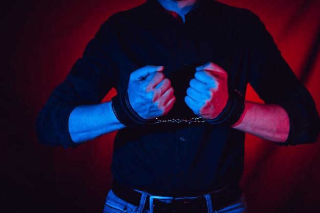 Een man overhandigt het dragen van een paar zwarte lederen handboeien