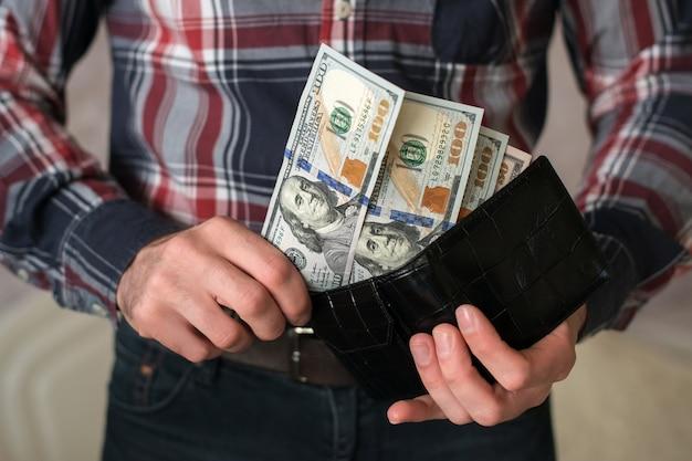 Een man pakt geld uit een portemonnee