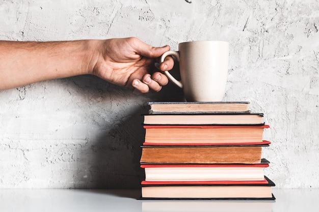 Een man pakt koffie van een stapel boeken. onderwijs, leren, lezen, hobby's