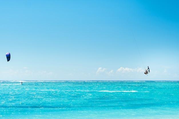 Een man paragliding op het strand van le morne, mauritius, indische oceaan op het eiland mauritius.