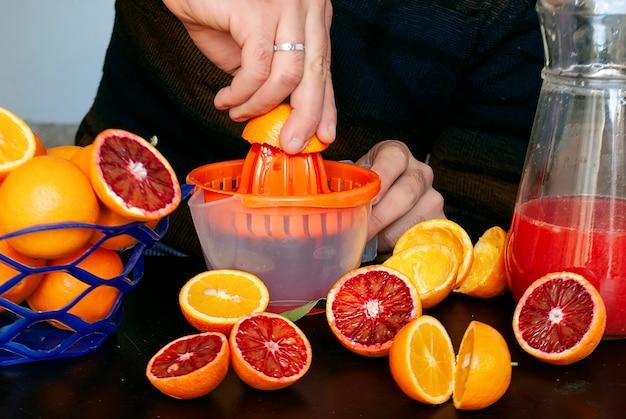 Een man perst sinaasappelsap in een sapcentrifuge, een mand met sinaasappels, gehalveerde sinaasappels, sinaasappelschillen en een karaf sinaasappelsap naast de sapcentrifuge.