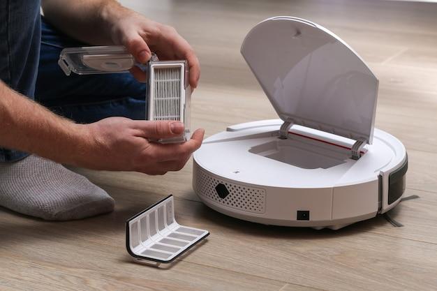 Een man plaatst een filter en een bak om stof en vuil op te vangen in de robotstofzuiger