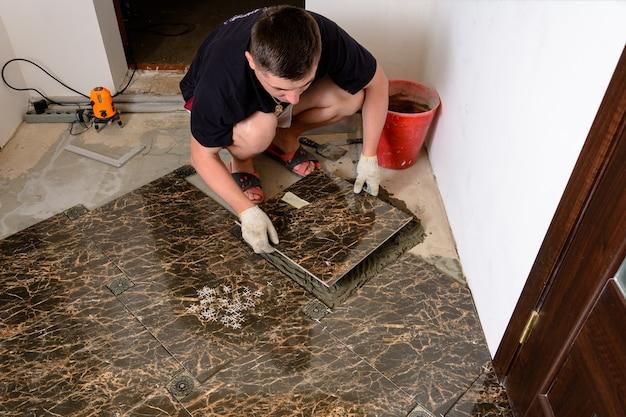 Een man plaatst een keramische tegel onder druk op een lijm in een bruine kamer