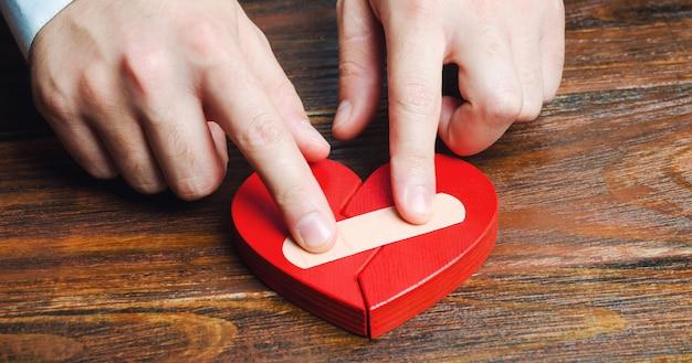 Een man plakt een rood hart met een pleister samen.