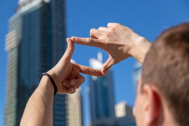 Een man plant een toekomstige foto en maakt een kader uit zijn vingers.