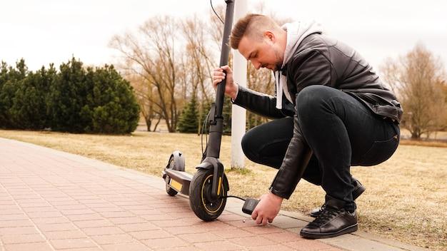 Een man pompt met een speciaal apparaat lucht in het stuur van een elektrische scooter