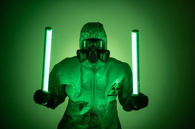 Een man poseert in beschermend pak terwijl hij op groen staat en een groene uraniumlamp vasthoudt