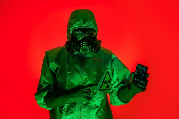Een man poseert in een beschermend pak met een beschermend gasmasker in zijn hand.