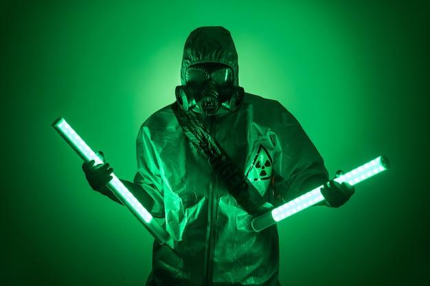 Een man poseert in een beschermend pak met een capuchon op zijn hoofd, met een beschermend gasmasker, poseren terwijl hij tegen een groene achtergrond staat, met uraniumlampen in haar gescheiden handen. gevaar