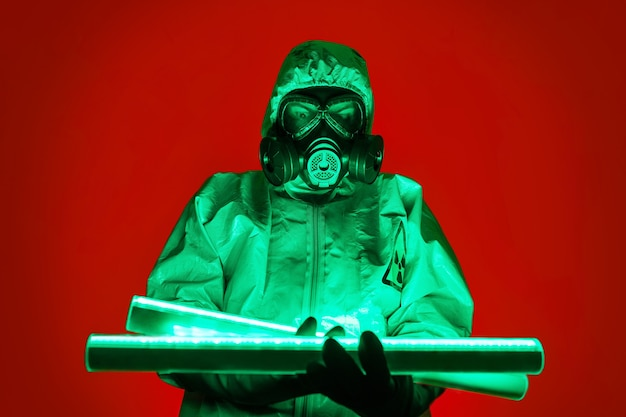 Een man poseert in een geel beschermend pak met een capuchon op zijn hoofd, met een beschermend gasmasker, staande tegen een rode achtergrond, zichzelf verlichtend met groene uraniumlampen.