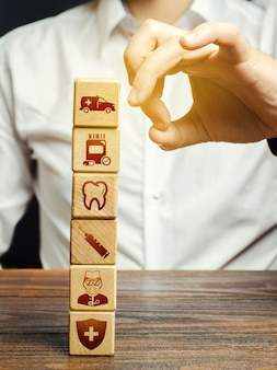 Een man probeert een toren van blokken met attributen van medicijnsymbolen neer te halen