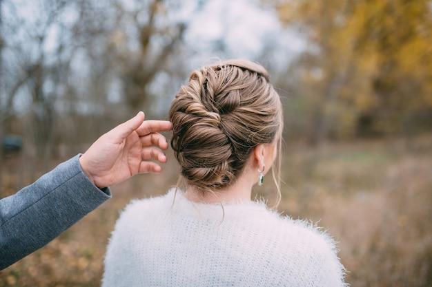 Een man raakt het haar van een vrouw met zijn hand aan, close-up