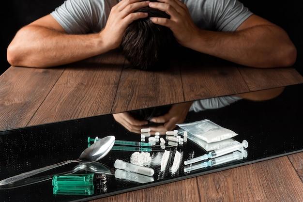 Een man reikt naar drugs. de strijd tegen drugsverslaving.