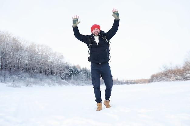 Een man reist met een rugzak. winterwandeling in het bos. toerist op een wandeling in de winter in het park.