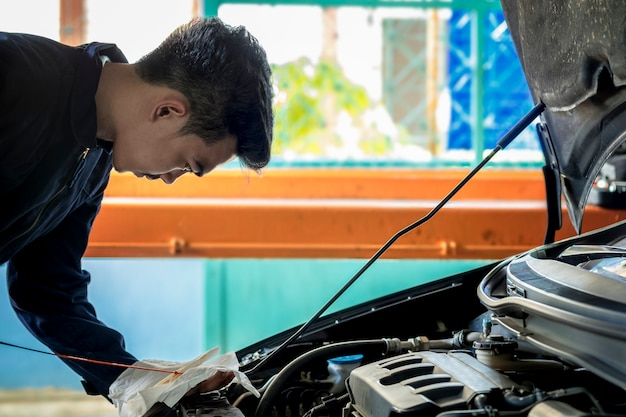 Een man repareer auto. regelmatige autoverzorging maakt autogebruik. veilig en zelfverzekerd in het rijden. regelmatige inspectie van gebruikte auto's. het is heel goed gedaan. zoals oliecontrole.
