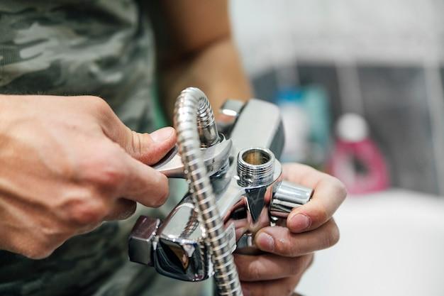 Een man repareert een kraan
