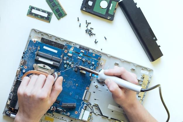 Een man repareert een laptop, demonteert een laptop op een witte muur, soldeert het moederbord van de laptop