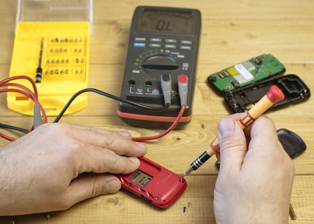 Een man repareert een mobiele telefoon op de tafel.