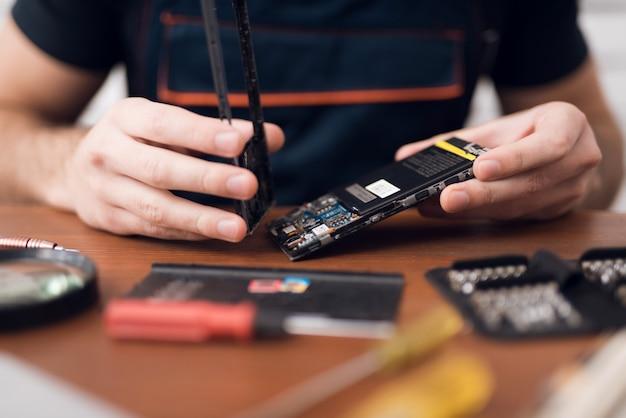 Een man repareert een mobiele telefoon op het werk