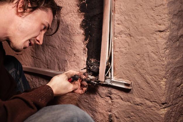 Een man repareert een verbrande stopcontact. kortsluiting, verbrande draden. sporen van rookvuur op de muur. het stopcontact was volledig gesmolten, de spanning daalde door het gebruik van een elektrische kachel. schroevendraaier