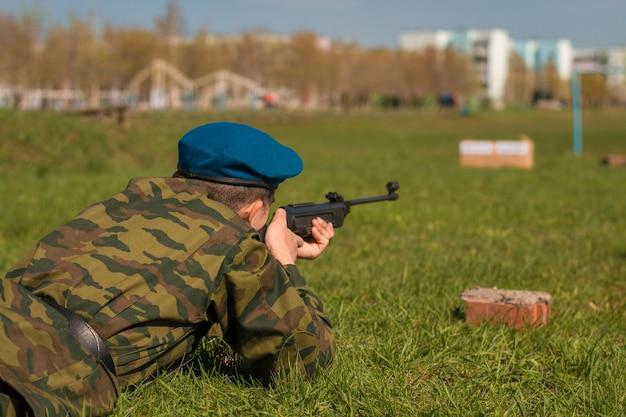 Een man richt op een doelwit. sniper ligt op het gras en schiet vanuit een machinegeweer.