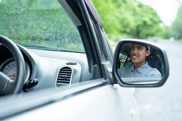 Een man rijdt in een auto die zichtbaar is vanuit de achteruitkijkspiegel