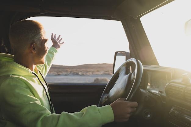 Een man rijdt in zijn auto en kijkt en geniet van de prachtige landschapszonsondergang - jonge tiener die een auto bestuurt - plezier heeft in zijn vakanties die reizen in een tour