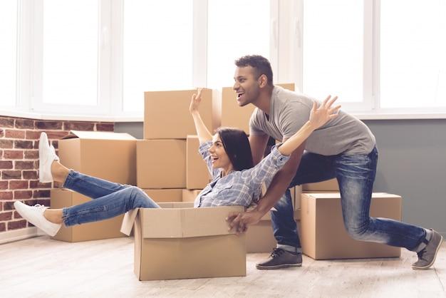 Een man rolt een meisje in een doos in een nieuw appartement.