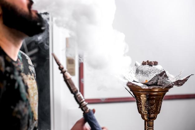 Een man rookt shisha met een sinaasappel en rook rond