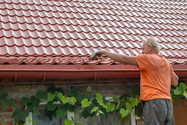 Een man ruimt puin en bladeren op uit het dakgootsysteem op het dak van zijn huis.