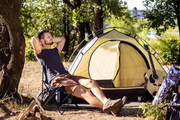 Een man rust bij een tent op een klapstoel in het bos.
