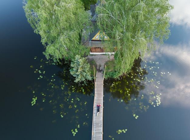 Een man rust op de brug bij de rivier. bovenaanzicht van de rustende visser en een huis op het eiland.