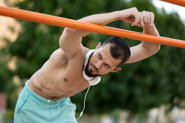 Een man rust uit na het doen van push-ups op de tralies buiten op de dag