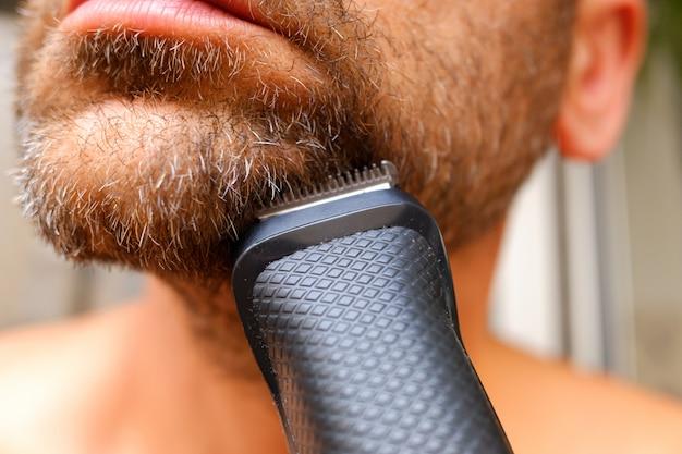 Een man scheert zijn baard met een elektrisch scheerapparaat.