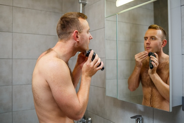 Een man scheert zijn gezicht met een elektrisch scheerapparaat voor een spiegel. huidirritatie. bad procedure