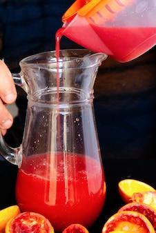 Een man schenkt vers sinaasappelsap uit een sapcentrifuge in een kan en sinaasappelschillen rondom.