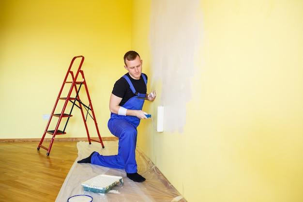 Een man schildert de muur in het huis met een roller en verf. renovatie van kamers in het huis.