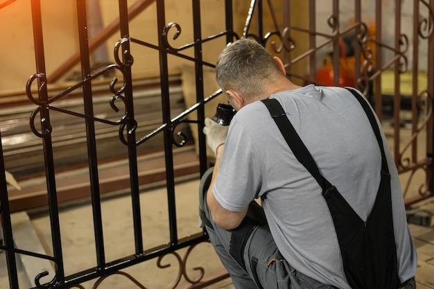 Een man schildert een met de hand gemaakt smeedijzeren hek.
