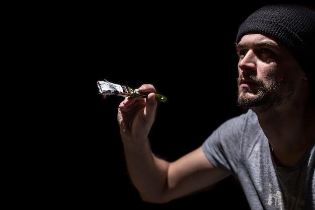 Een man schildert een penseel met witte verf op een zwarte muur