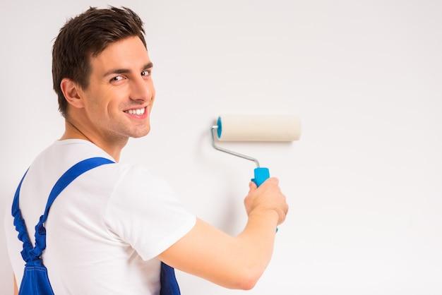 Een man schildert een witte muur en glimlacht.