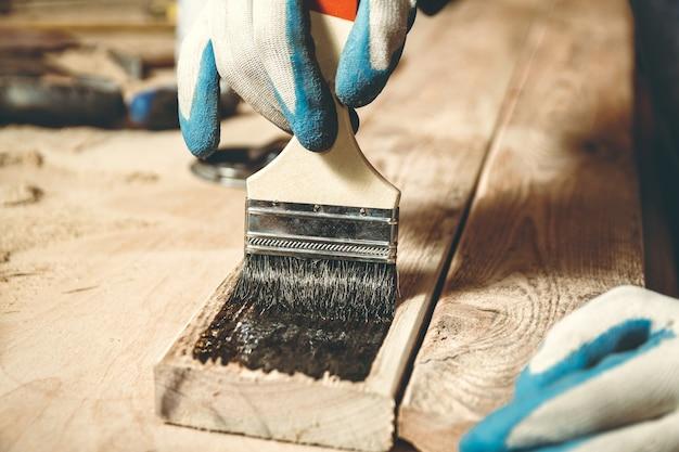 Een man schildert in een werkplaats een handgemaakt houten product met verf