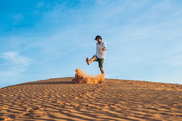 Een man schopt zand in een rode woestijn. splash van woede concept.