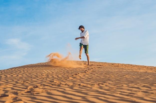 Een man schopt zand in een rode woestijn. splash van woede concept