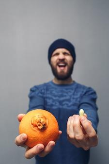 Een man schreeuwt in problemen vanwege aambeien. een bebaarde man heeft een sinaasappel en een zetpil voor aambeien in zijn handen. aambeien concept.