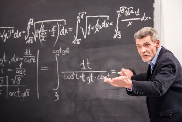 Een man schrijft een formule en vraagt hem om het uit te leggen.