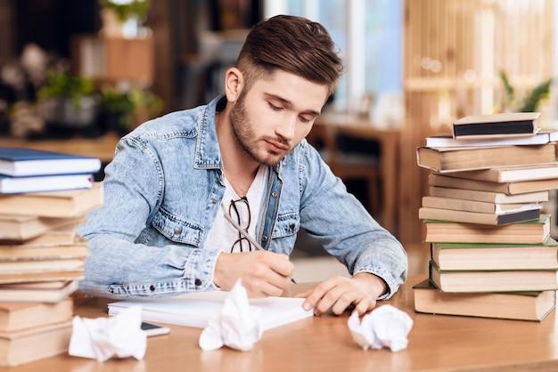 Een man schrijft iets op een vel papier om hem heen.