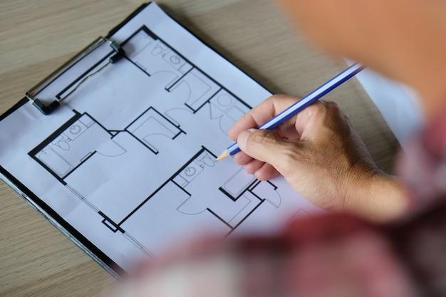 Een man schrijft of controleert de blauwdruk van het huis