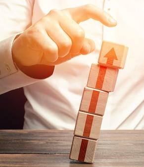 Een man slaat een toren van blokken omver met een pijl omhoog.